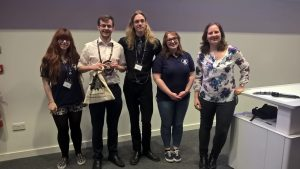 Fraser Baird (second from left) smiling with the committee of CAPS 2016 as he receives his prize - a ScienceGrrl goody bag - from Director Dr Heather Williams (far right)