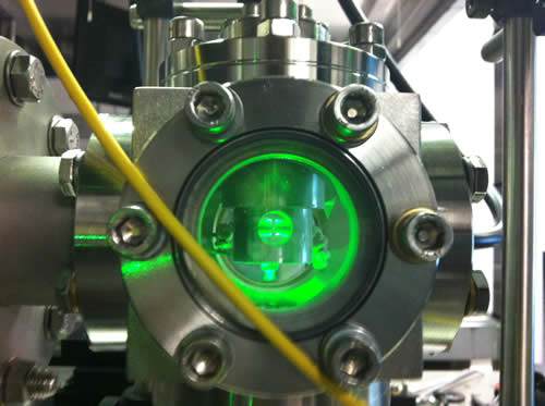 An ion trap levitating a 10um diameter glass sphere, illuminated with a green laser. The sphere looks bigger than it actually is because of the light scattering off it